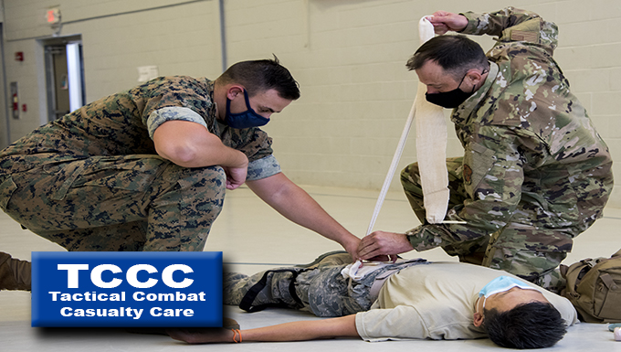 two service members bandage a simulated wound on an injured service member