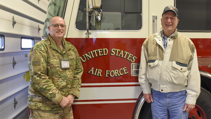 Master Sergeant Gary Shannon and Retired Chief Master Sergeant Edward Boyd pose in front of a fire department vehicle.