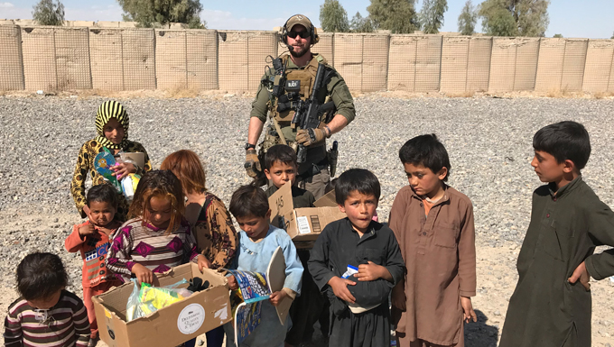 Master Sergeant Keith Gregory stands with a group of local children during a recent deployment to Kandahar, Afghanistan