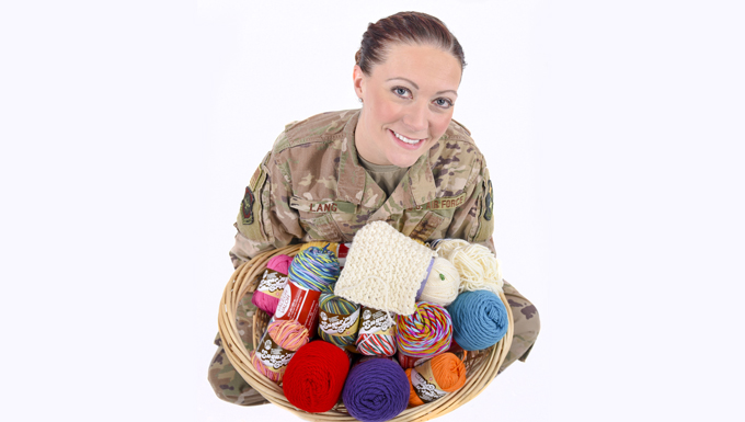 Tech. Sgt. Amber Lang sits holding a basket of Yarn